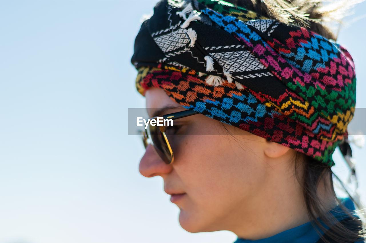 Side view of woman wearing headscarf looking away
