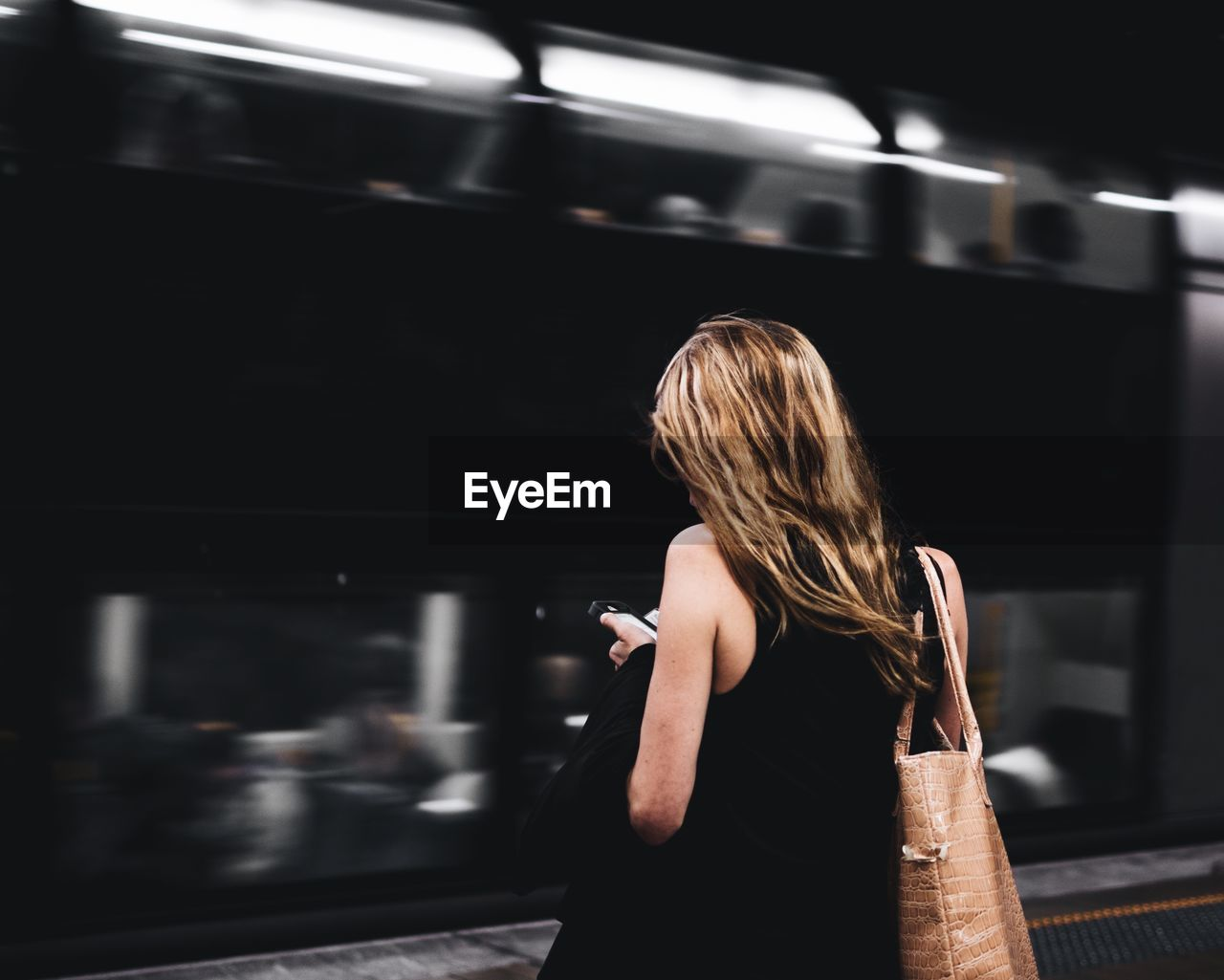 Rear view of woman using mobile phone at railroad station platform