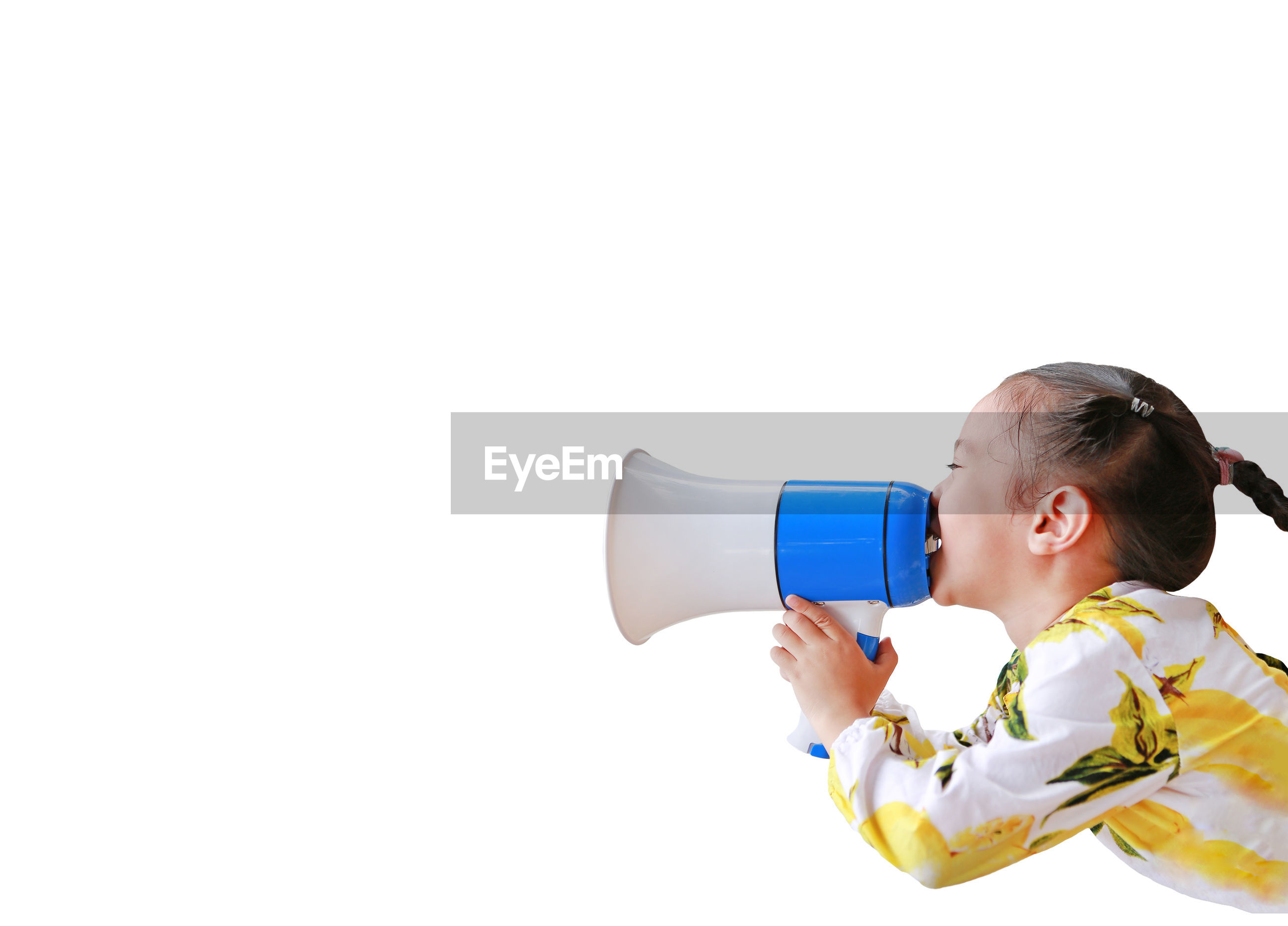 Side view of girl speaking on megaphone against white background