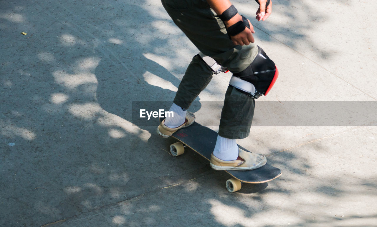 real people, low section, one person, lifestyles, day, leisure activity, human leg, shoe, shadow, sunlight, human body part, casual clothing, high angle view, body part, outdoors, city, nature, sport, transportation, riding, jeans