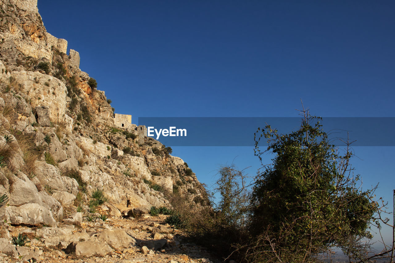 sky, rock, plant, clear sky, solid, nature, rock - object, blue, rock formation, tree, low angle view, day, no people, mountain, scenics - nature, beauty in nature, tranquility, tranquil scene, copy space, non-urban scene, outdoors, formation, arid climate