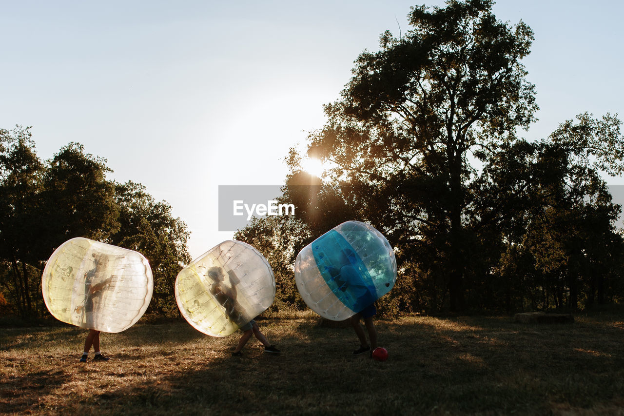 Friends playing in bubble football at park against clear sky