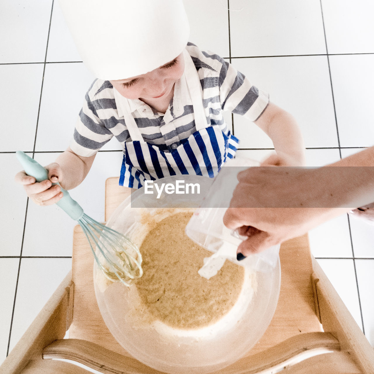 High angle cropped hand of woman pouring water while boy mixing batter on wooden ladder