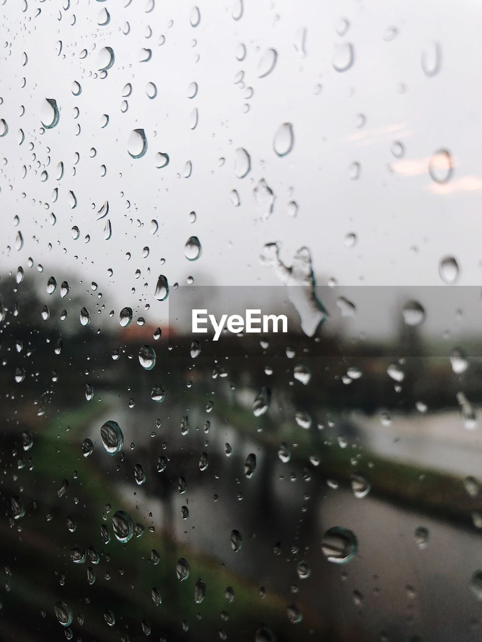 CLOSE-UP OF WET WINDOW AGAINST SKY