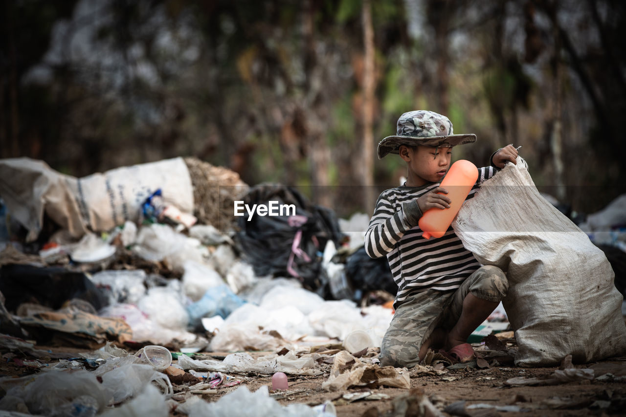 Cute boy sitting by garbage outdoors