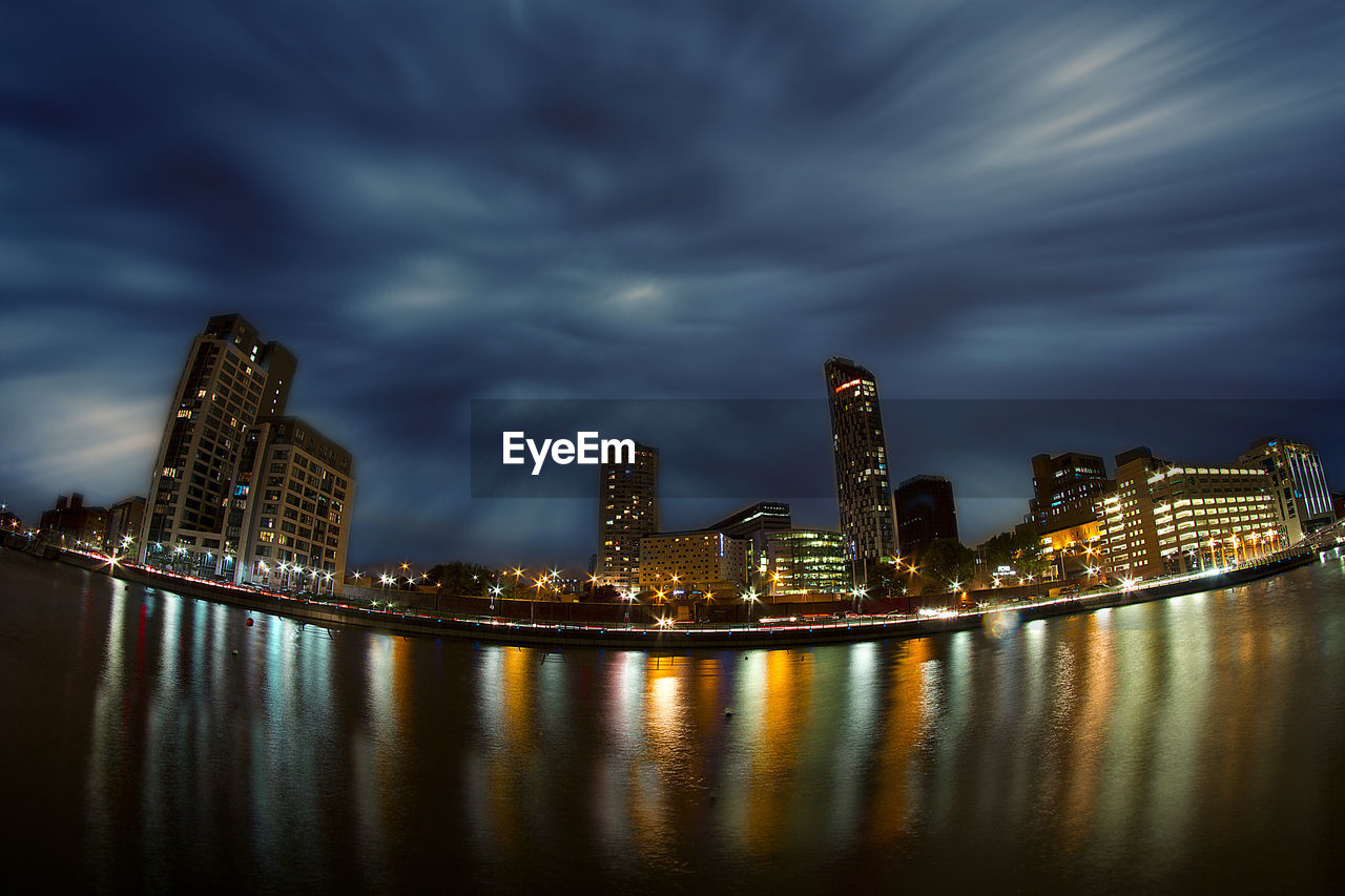 architecture, skyscraper, illuminated, built structure, building exterior, city, cloud - sky, cityscape, urban skyline, night, sky, modern, river, travel destinations, waterfront, no people, downtown district, storm cloud, outdoors, water