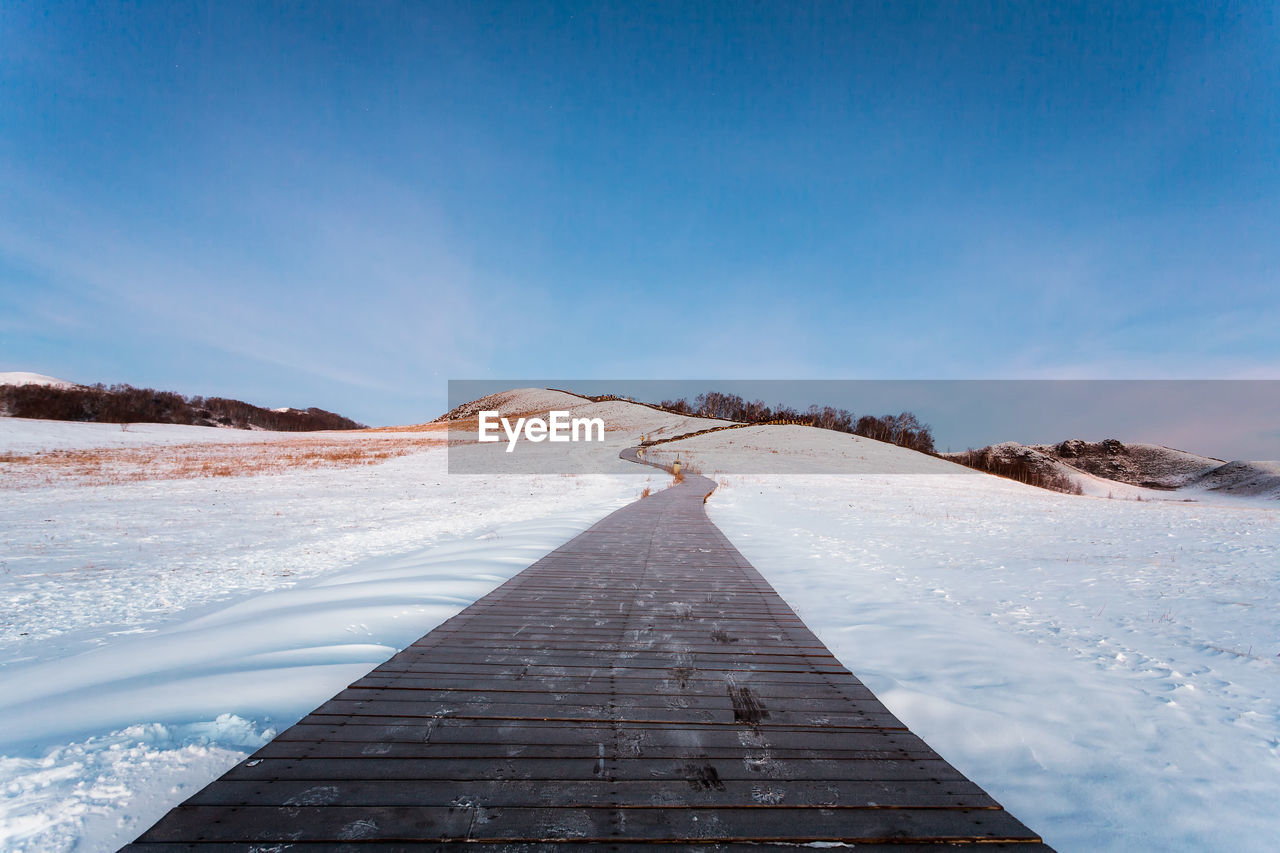 sky, direction, scenics - nature, snow, winter, cold temperature, blue, the way forward, tranquil scene, tranquility, mountain, nature, beauty in nature, no people, day, diminishing perspective, cloud - sky, non-urban scene, environment, outdoors, snowcapped mountain, surface level, long