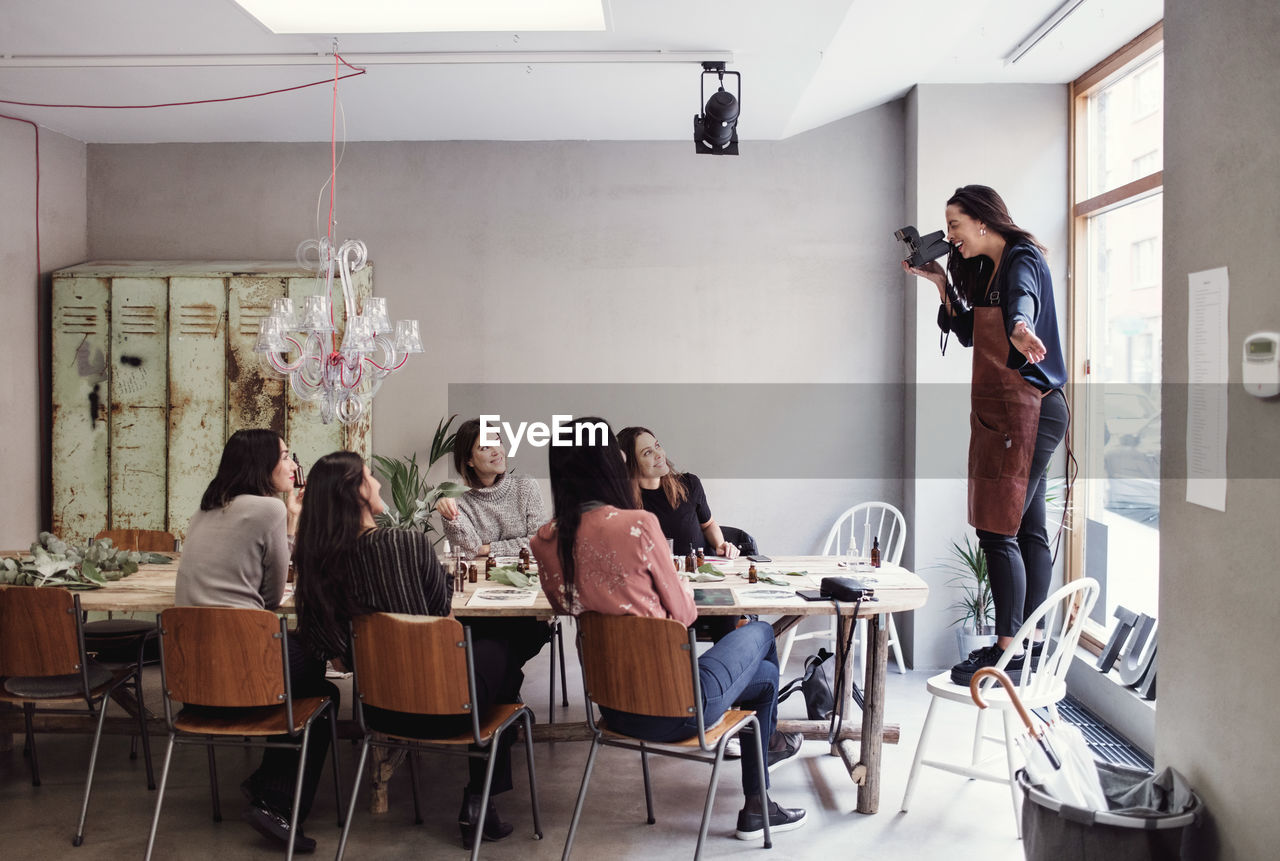 group of people, real people, women, men, table, indoors, seat, sitting, adult, young women, people, chair, young adult, standing, photography themes, technology, casual clothing, lifestyles, photographing, business, photographer