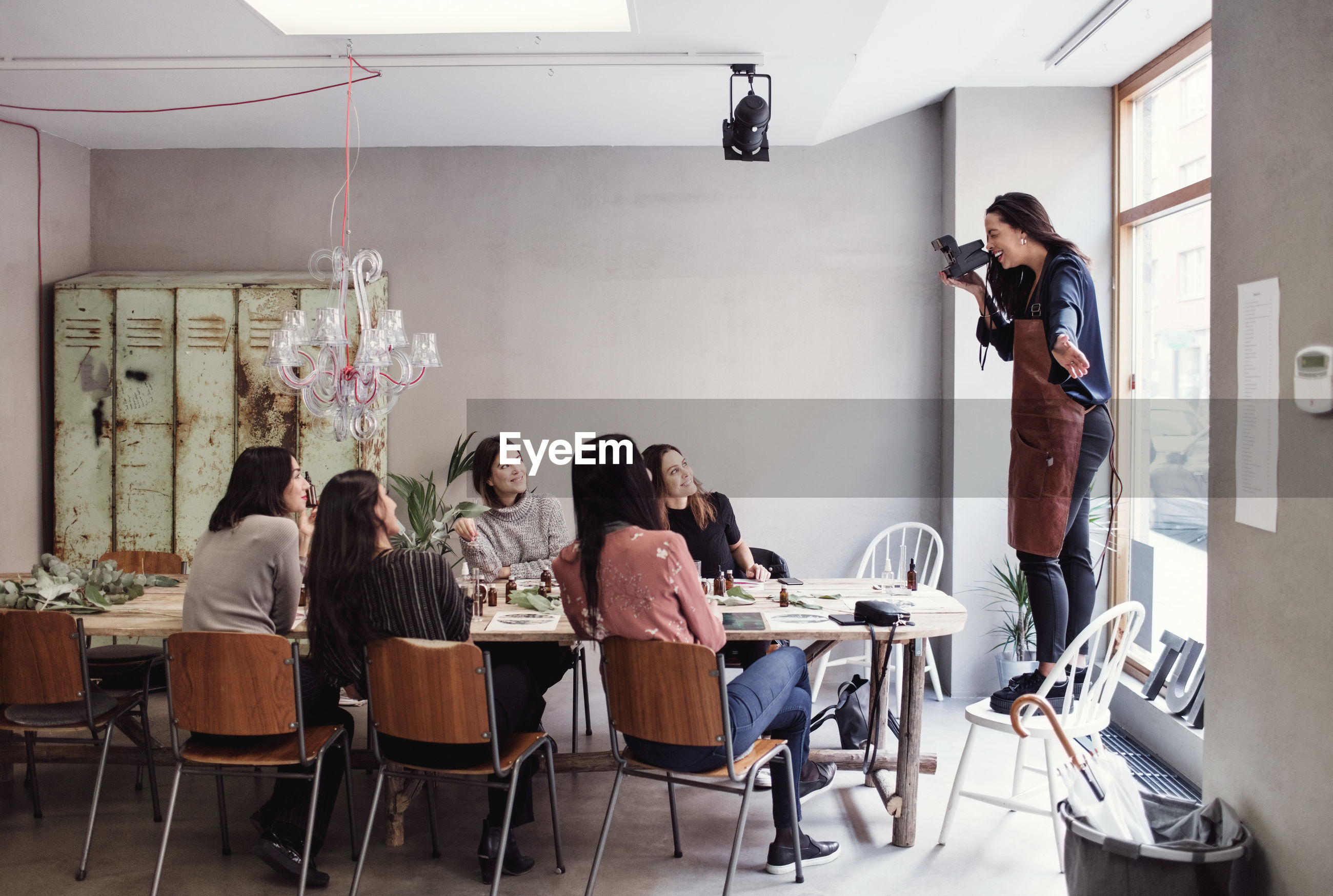 Cheerful woman standing on chair photographing female colleagues sitting at table in workshop