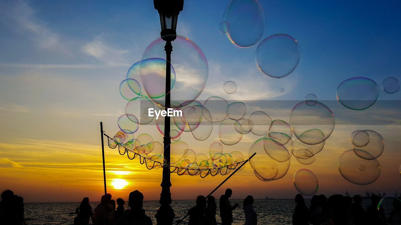 sky, sunset, real people, nature, beauty in nature, silhouette, cloud - sky, bubble, leisure activity, women, group of people, sea, lifestyles, people, water, scenics - nature, outdoors, beach, crowd