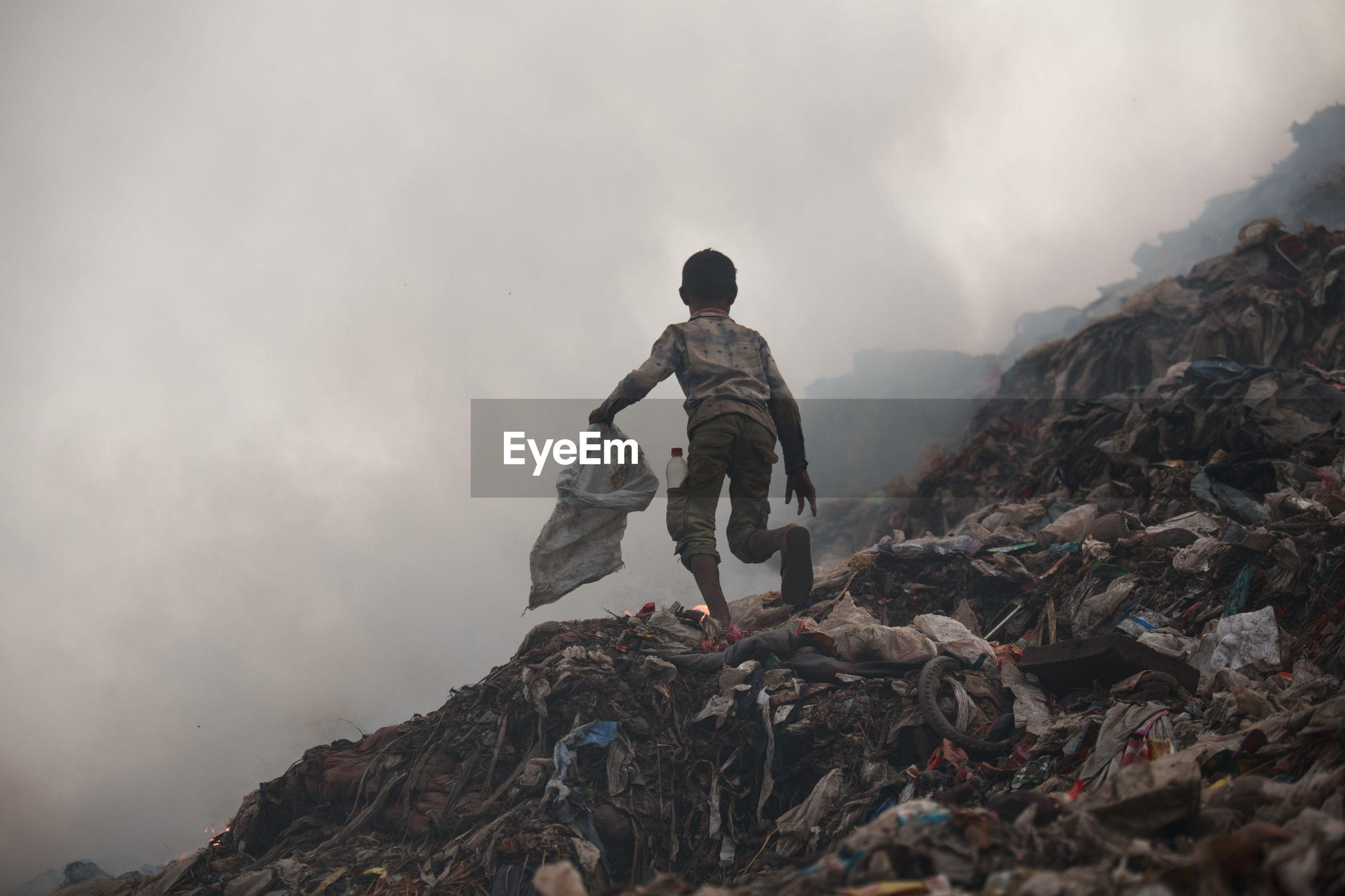 Full length of boy running on garbage dump against sky