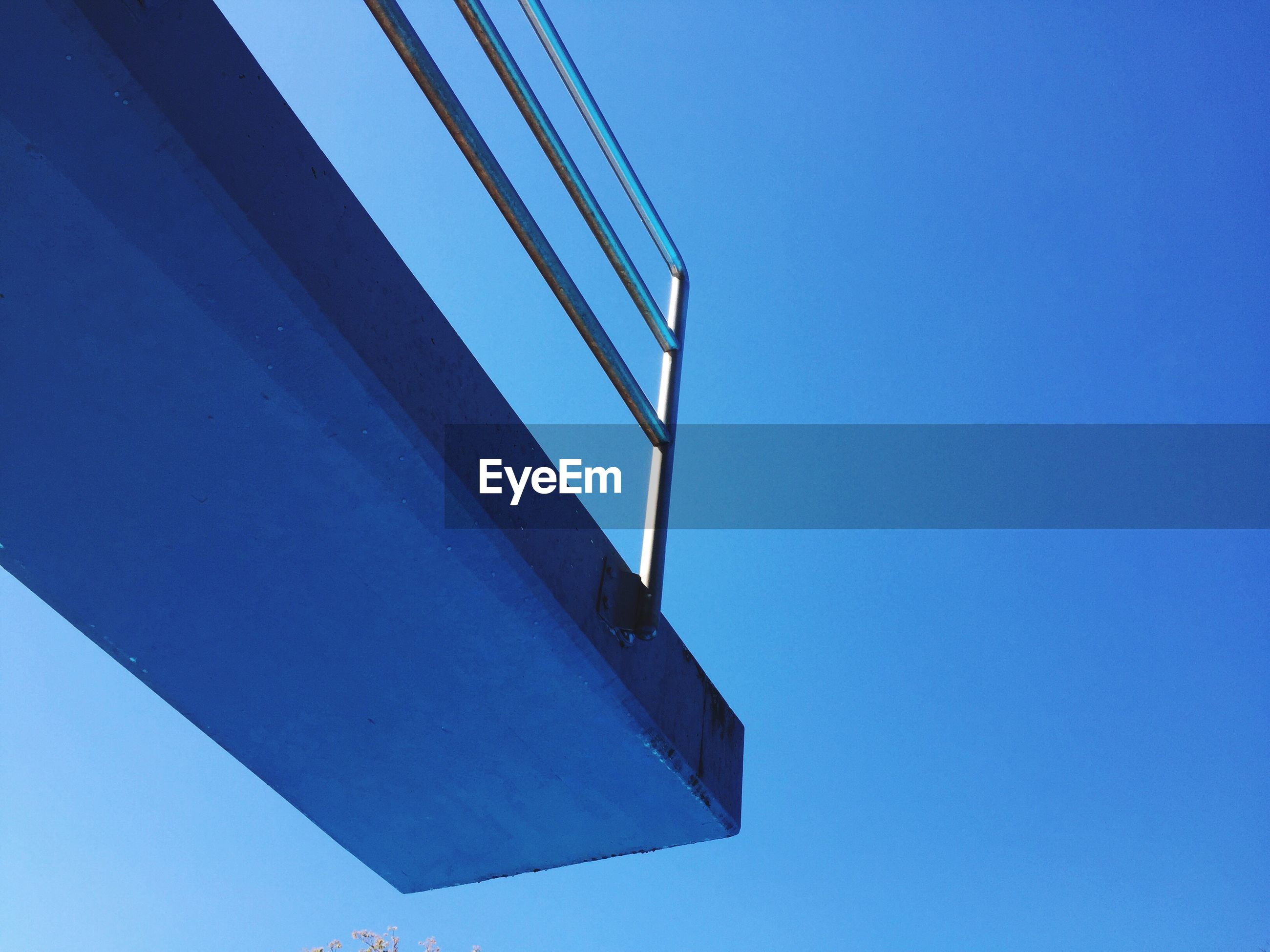 Low angle view of diving platform against clear blue sky