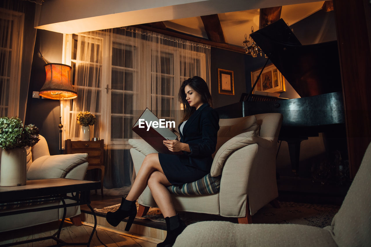 FULL LENGTH OF WOMAN SITTING ON SOFA IN ROOM