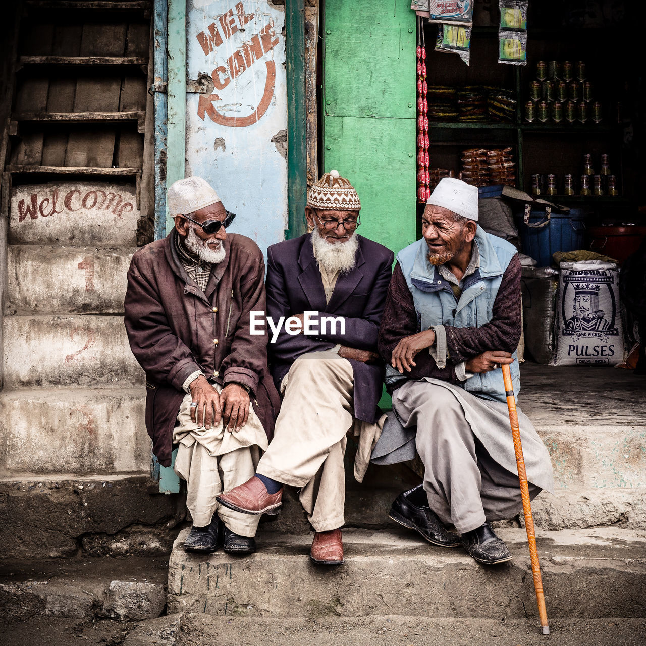 sitting, men, senior adult, full length, adult, real people, senior men, architecture, people, lifestyles, day, two people, clothing, males, women, front view, senior women, hat, communication, built structure, outdoors, social issues