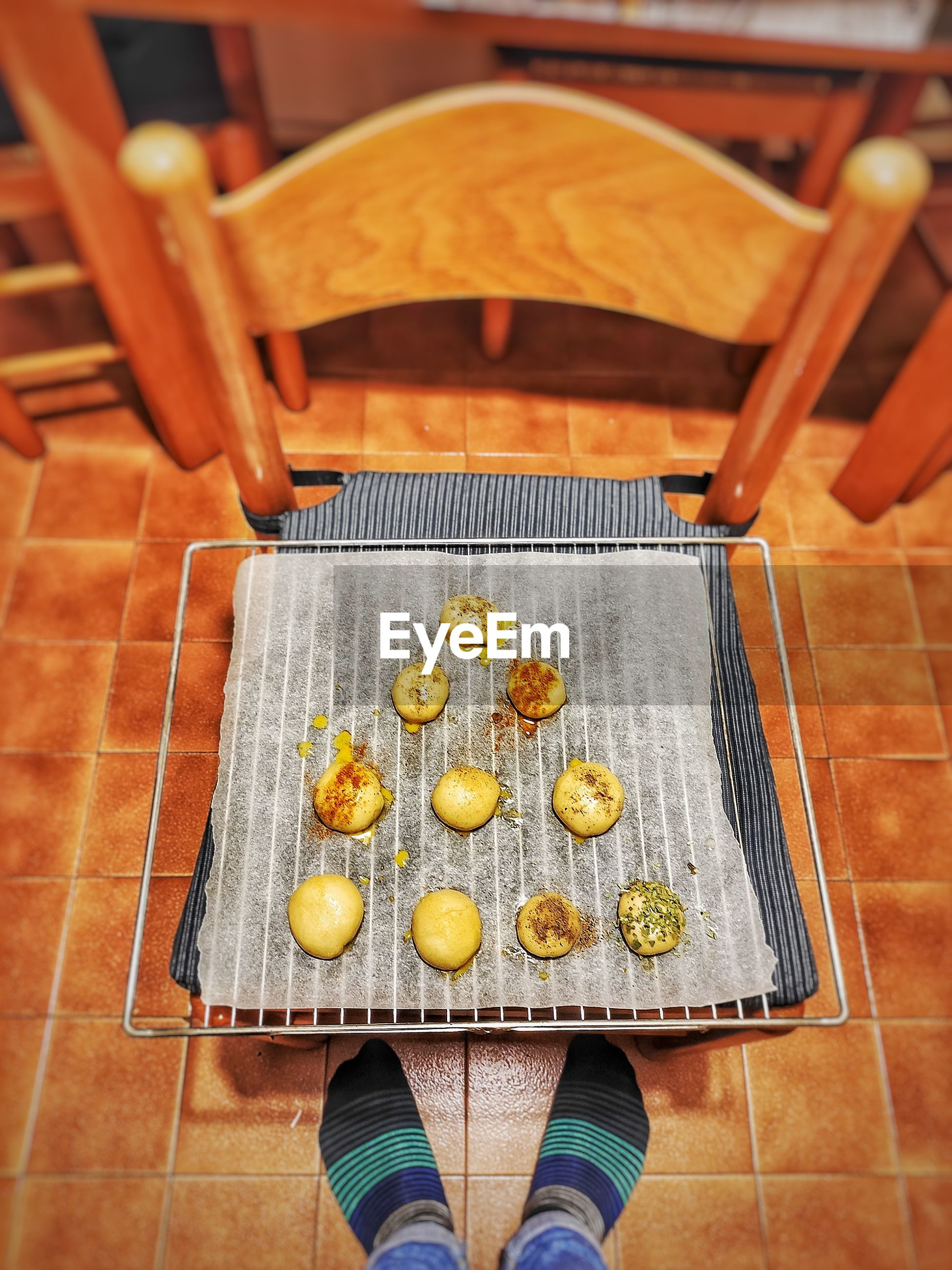 Low section of person standing on tiled floor by food