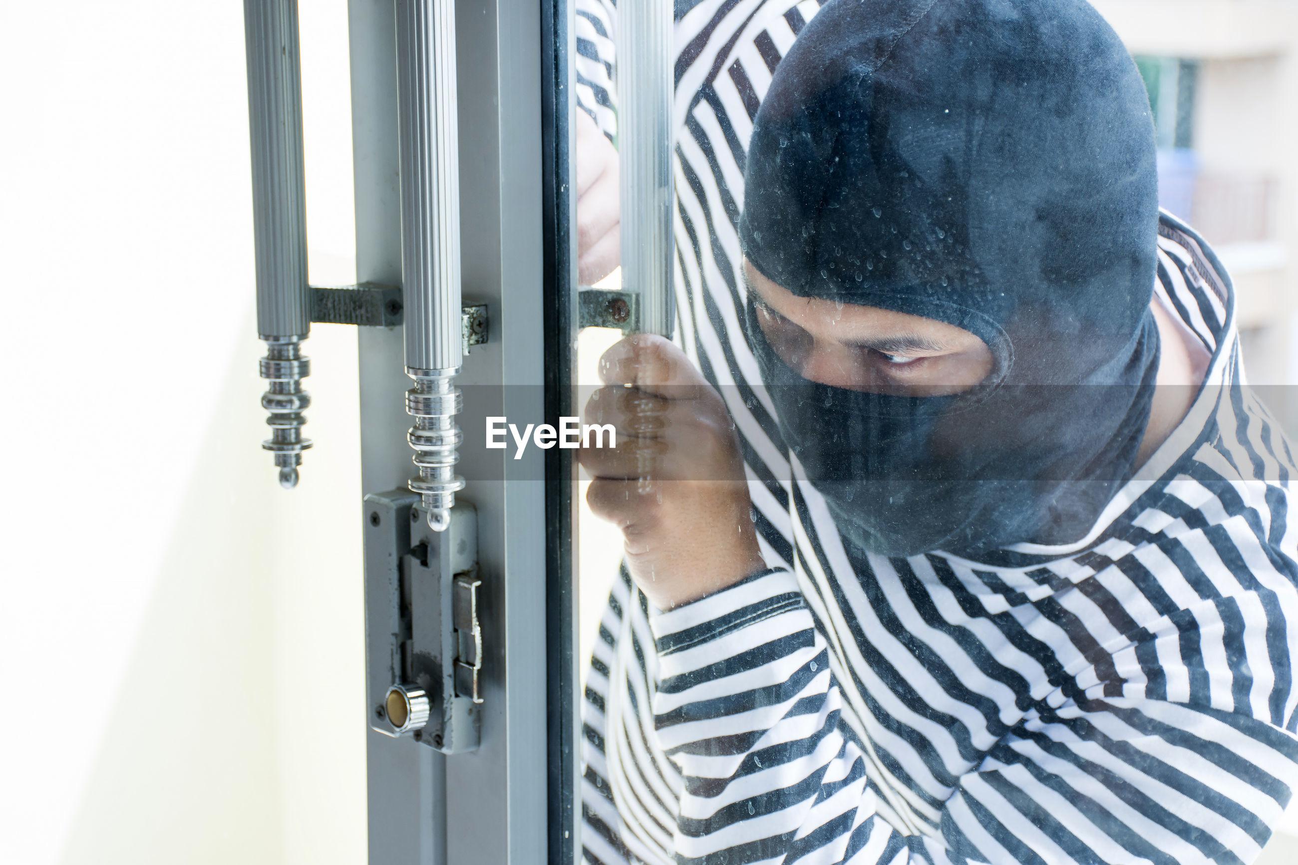 Thief looking through glass window
