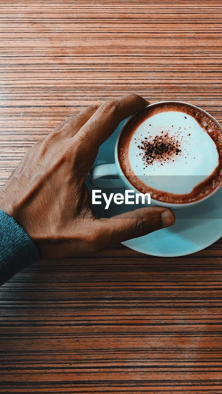 drink, refreshment, food and drink, one person, coffee, coffee - drink, coffee cup, cup, mug, human body part, human hand, hand, table, real people, indoors, holding, frothy drink, wood - material, hot drink, freshness, body part, finger, crockery