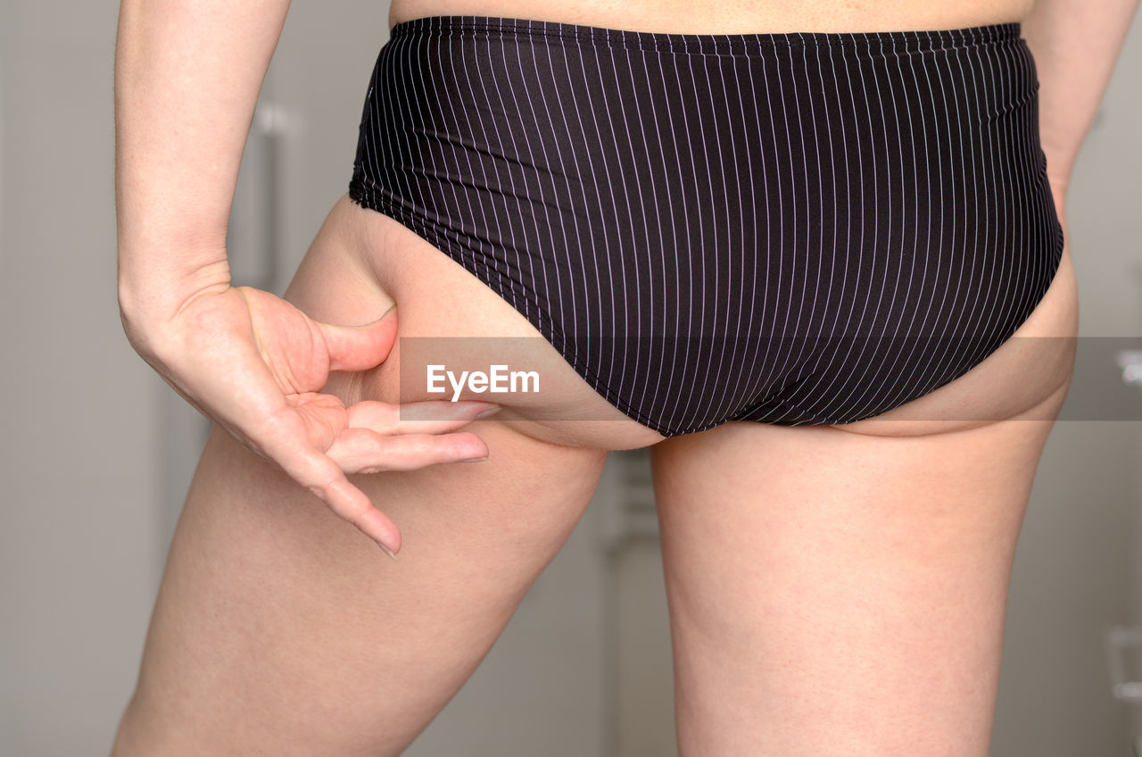 Midsection Of Woman Touching Cellulite On Body