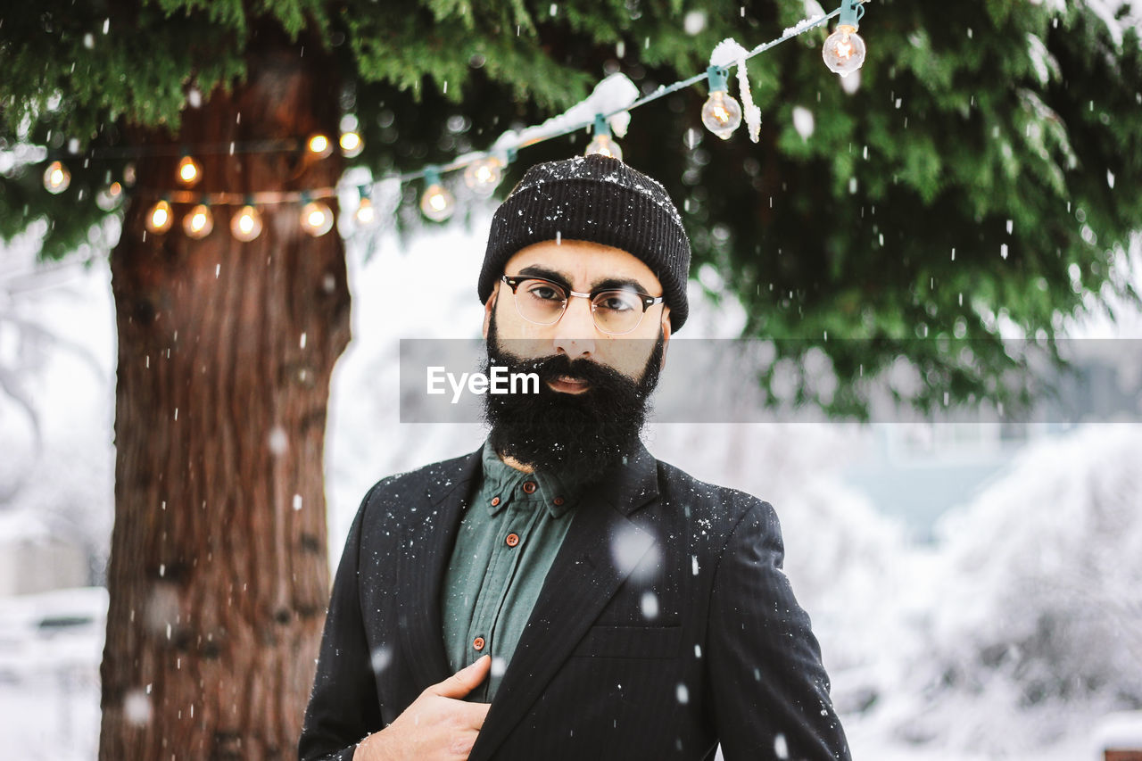 Portrait Of Young Man Standing Outdoors During Snowfall