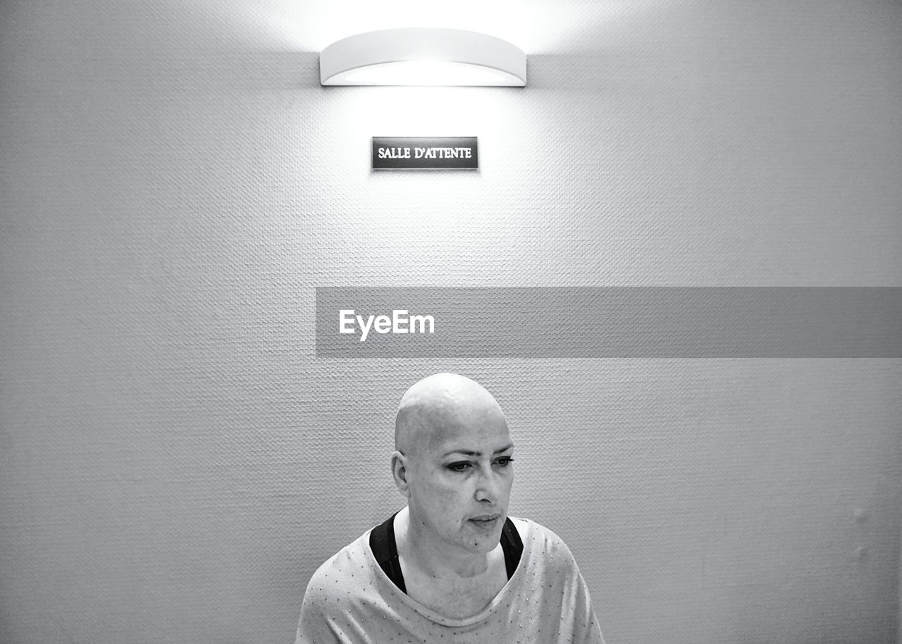 Shaved Head Woman Sitting Against Illuminated Wall At Hospital