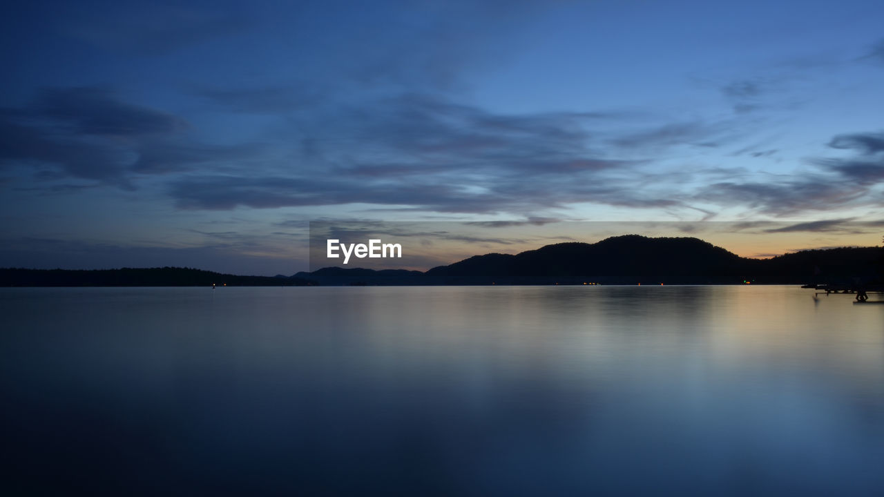 SCENIC VIEW OF LAKE BY SILHOUETTE MOUNTAIN AGAINST SKY