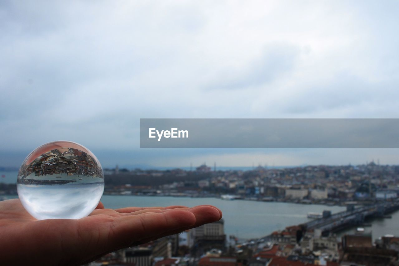 Cropped Image Of Hand Holding Crystal Ball With City In Background