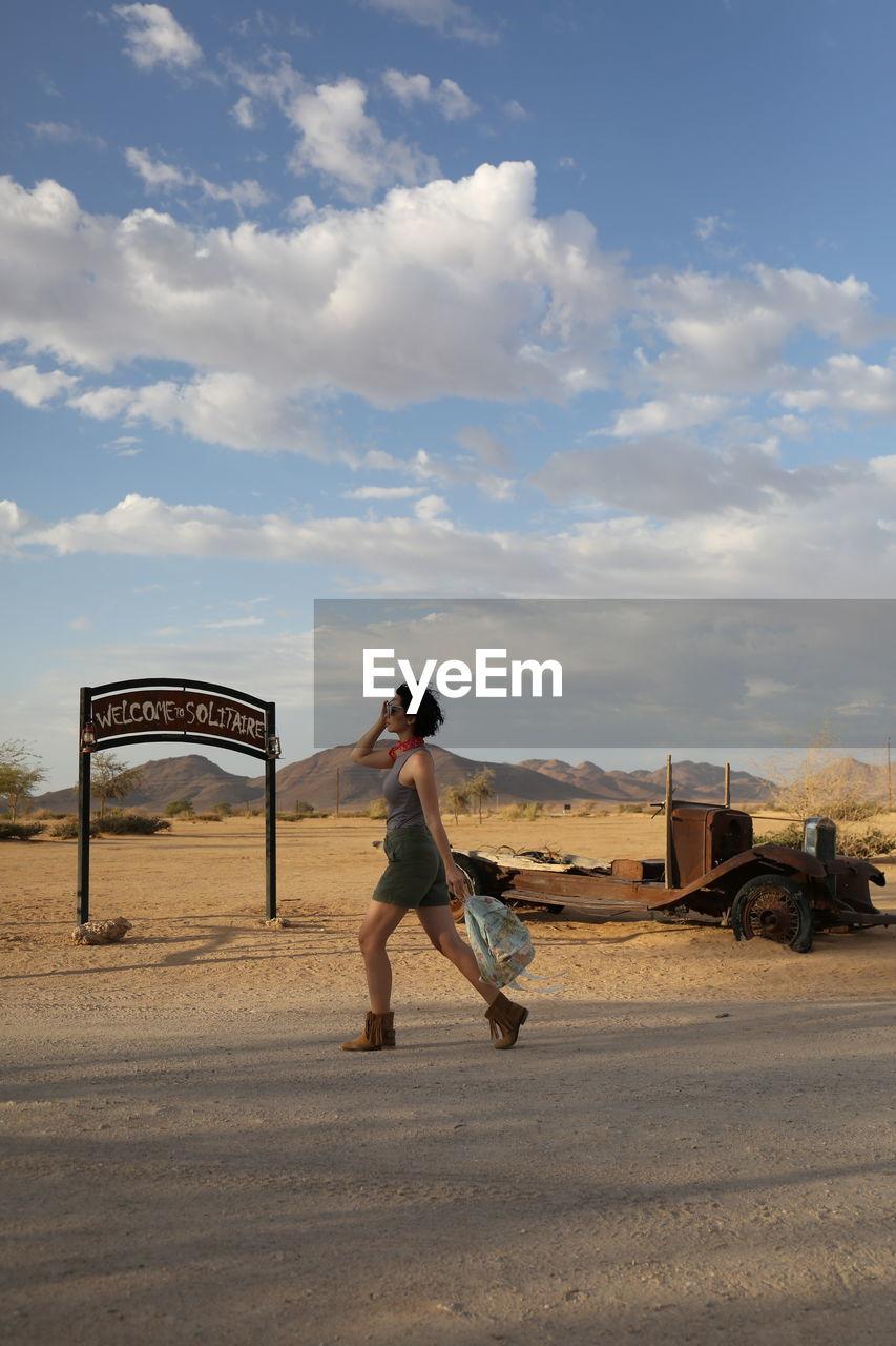 Full length of woman walking on road against sky