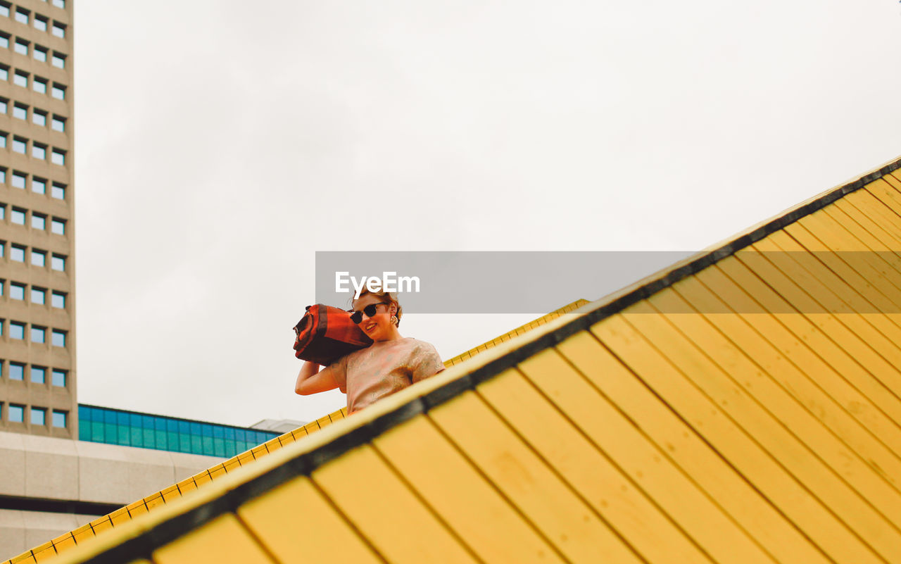 Low Angle View Of Young Woman Against Sky