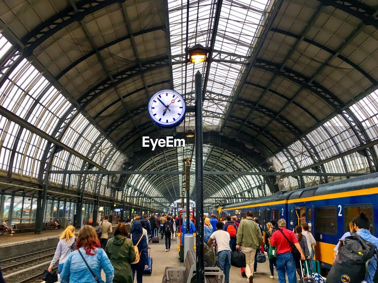 group of people, transportation, architecture, indoors, crowd, large group of people, mode of transportation, ceiling, clock, real people, travel, rail transportation, railroad station, time, illuminated, public transportation, women, railroad station platform, men, passenger, arch, waiting