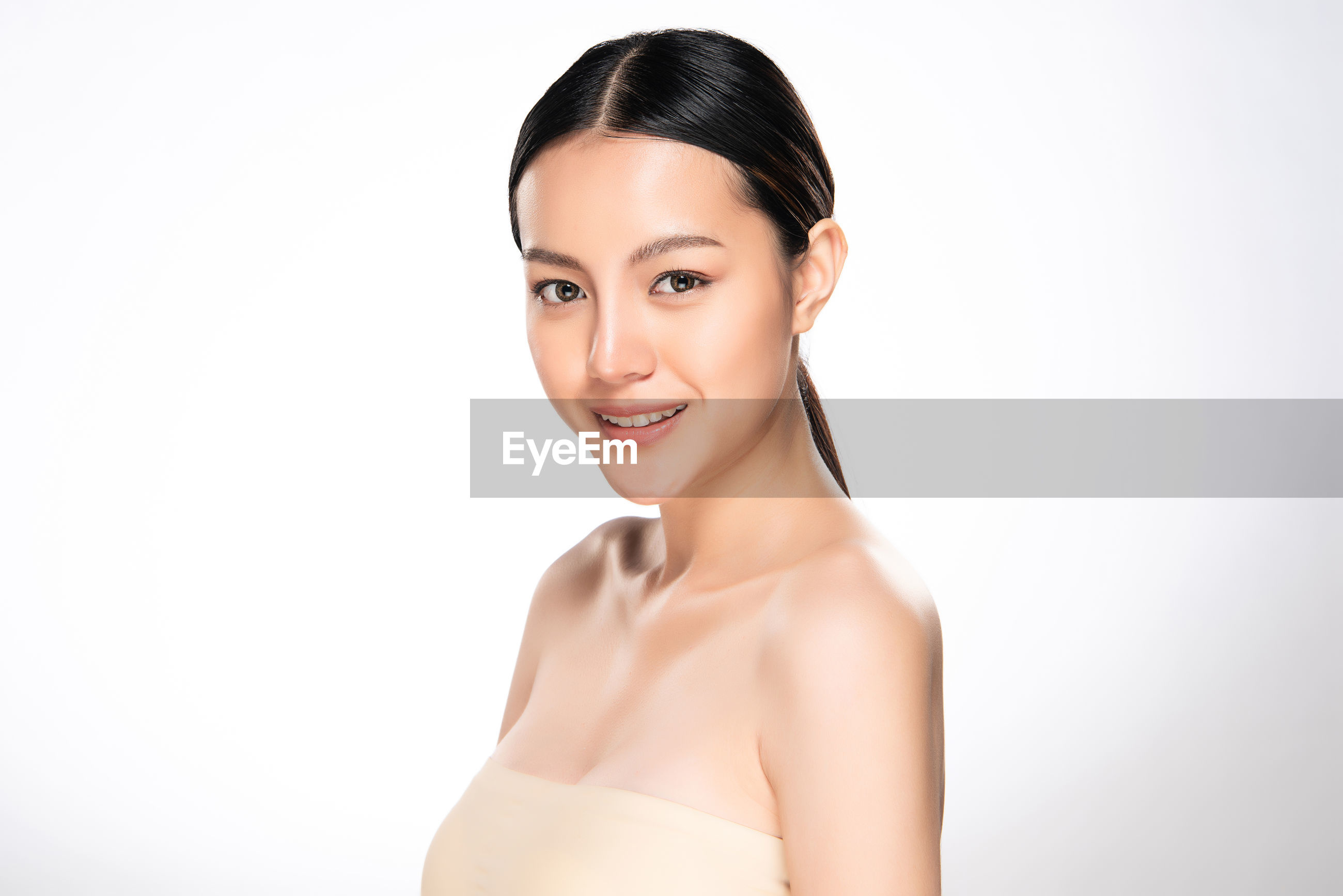 Portrait of smiling beautiful young woman against white background