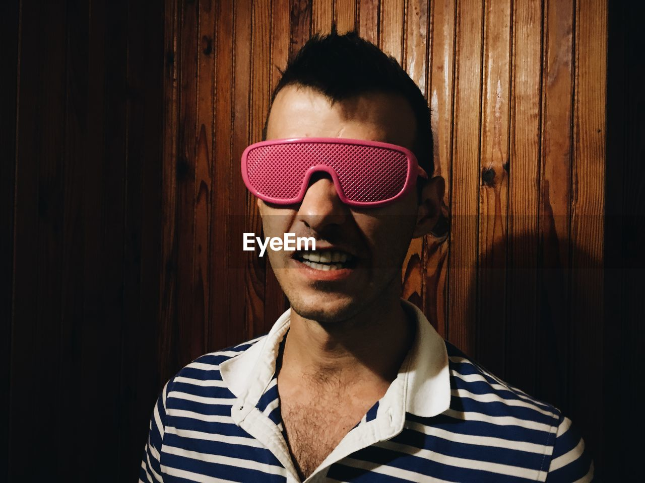 Young man wearing novelty glasses against wooden wall
