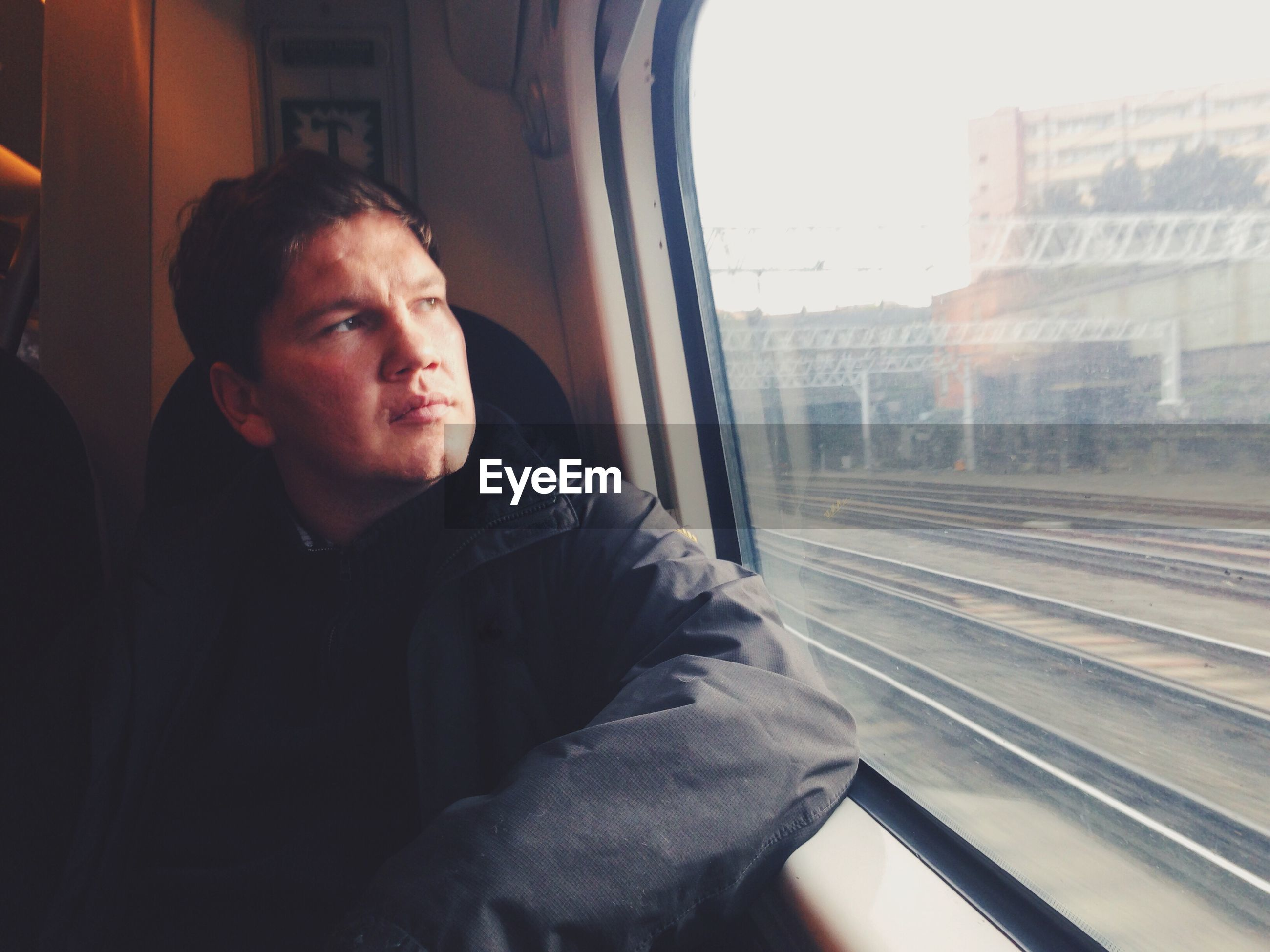 Man looking through window while travelling in train
