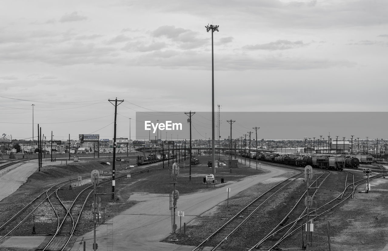 sky, transportation, cloud - sky, mode of transportation, rail transportation, nature, railroad track, track, no people, day, public transportation, high angle view, street light, built structure, outdoors, architecture, travel, lighting equipment, train, floodlight, shunting yard