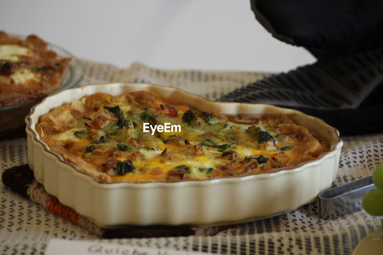 food and drink, food, freshness, ready-to-eat, indoors, close-up, indulgence, pizza, selective focus, unhealthy eating, baked, plate, still life, table, temptation, serving size, human hand, hand, one person, kitchen utensil, casserole, savory pie