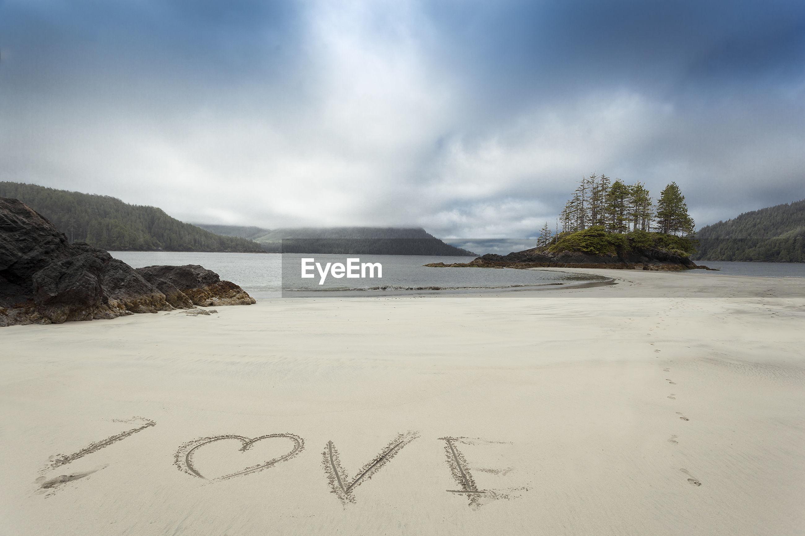 Text on sand at beach against sky