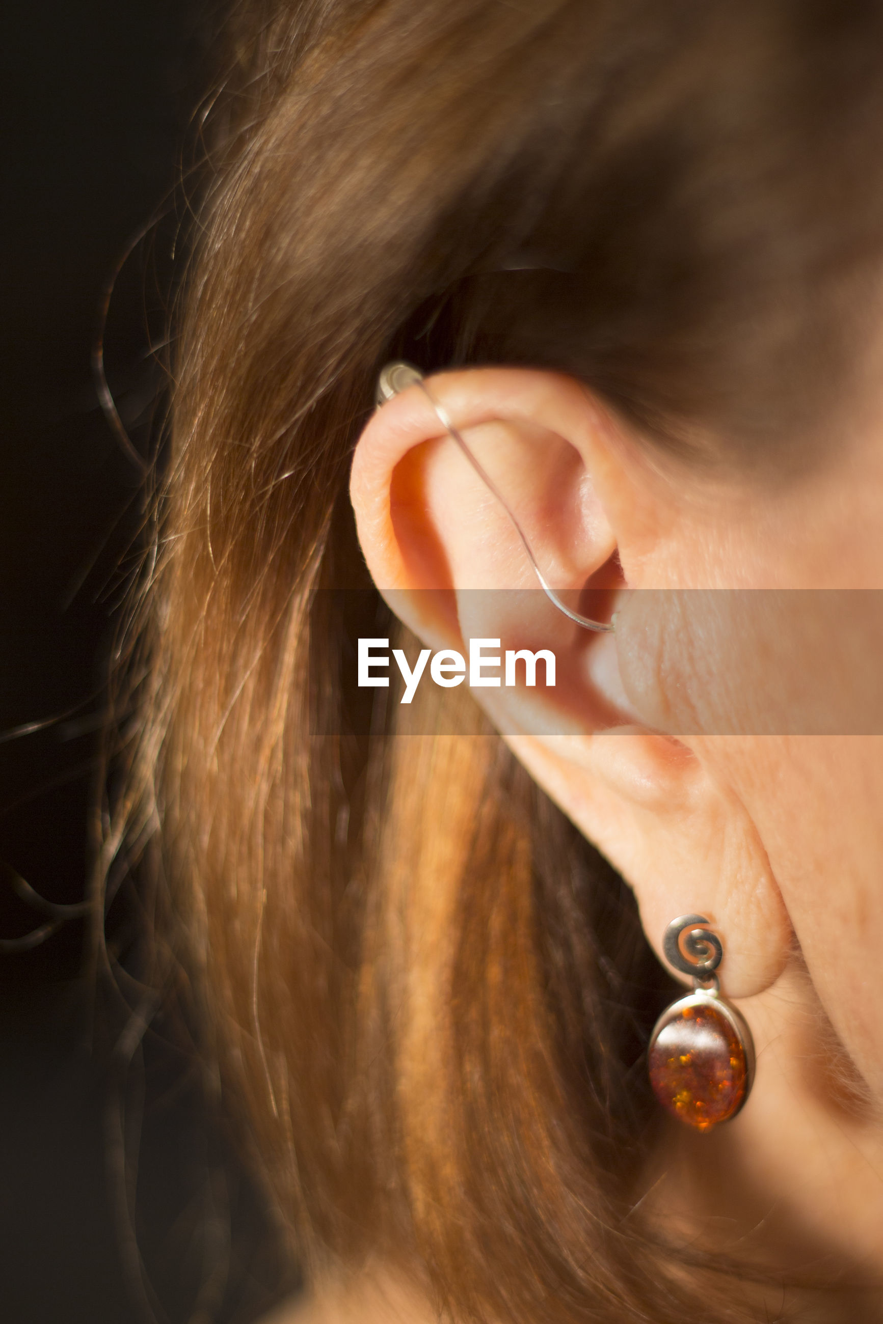 Close-up of woman with hearing aid on black background