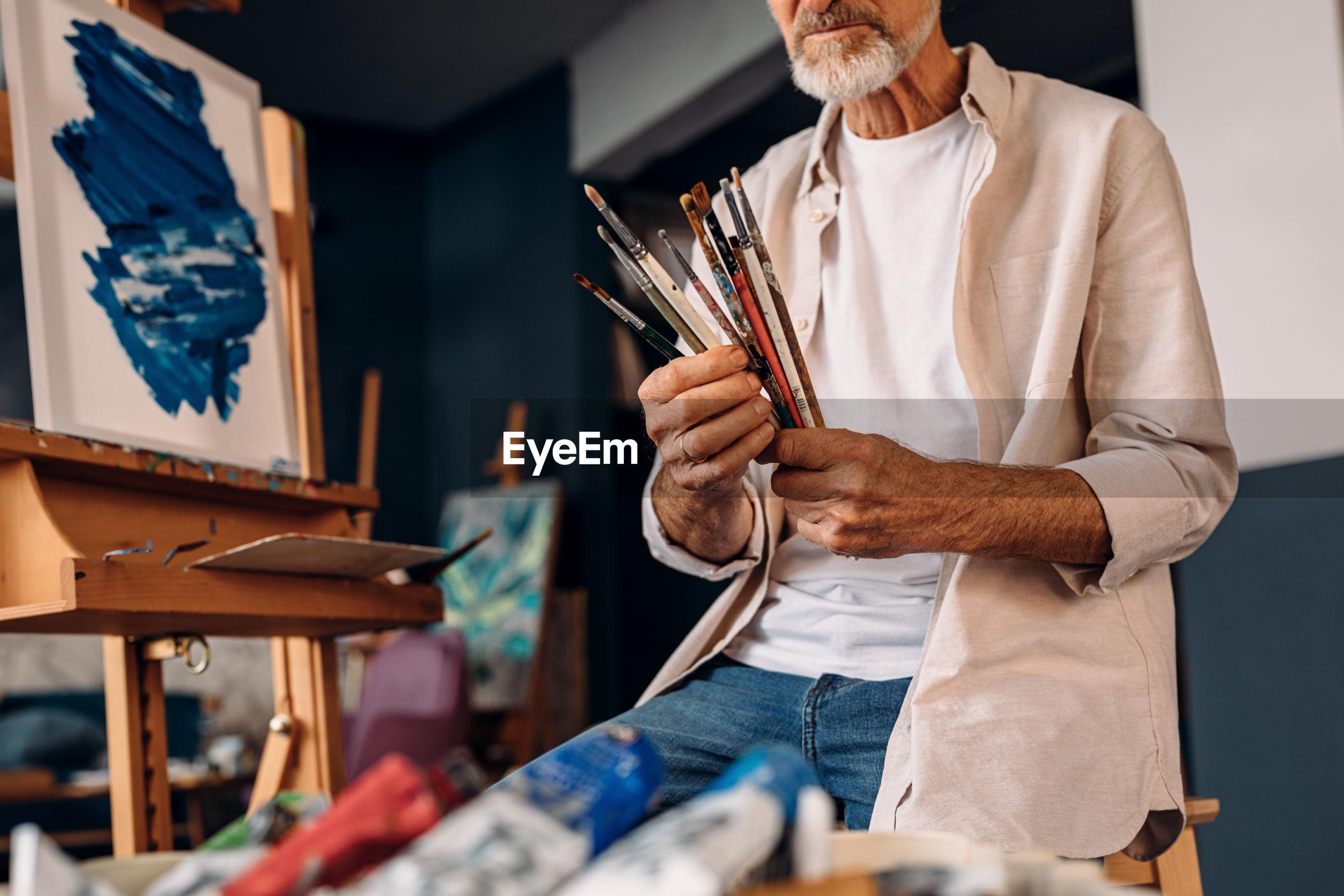 Senior man holding paintbrushes