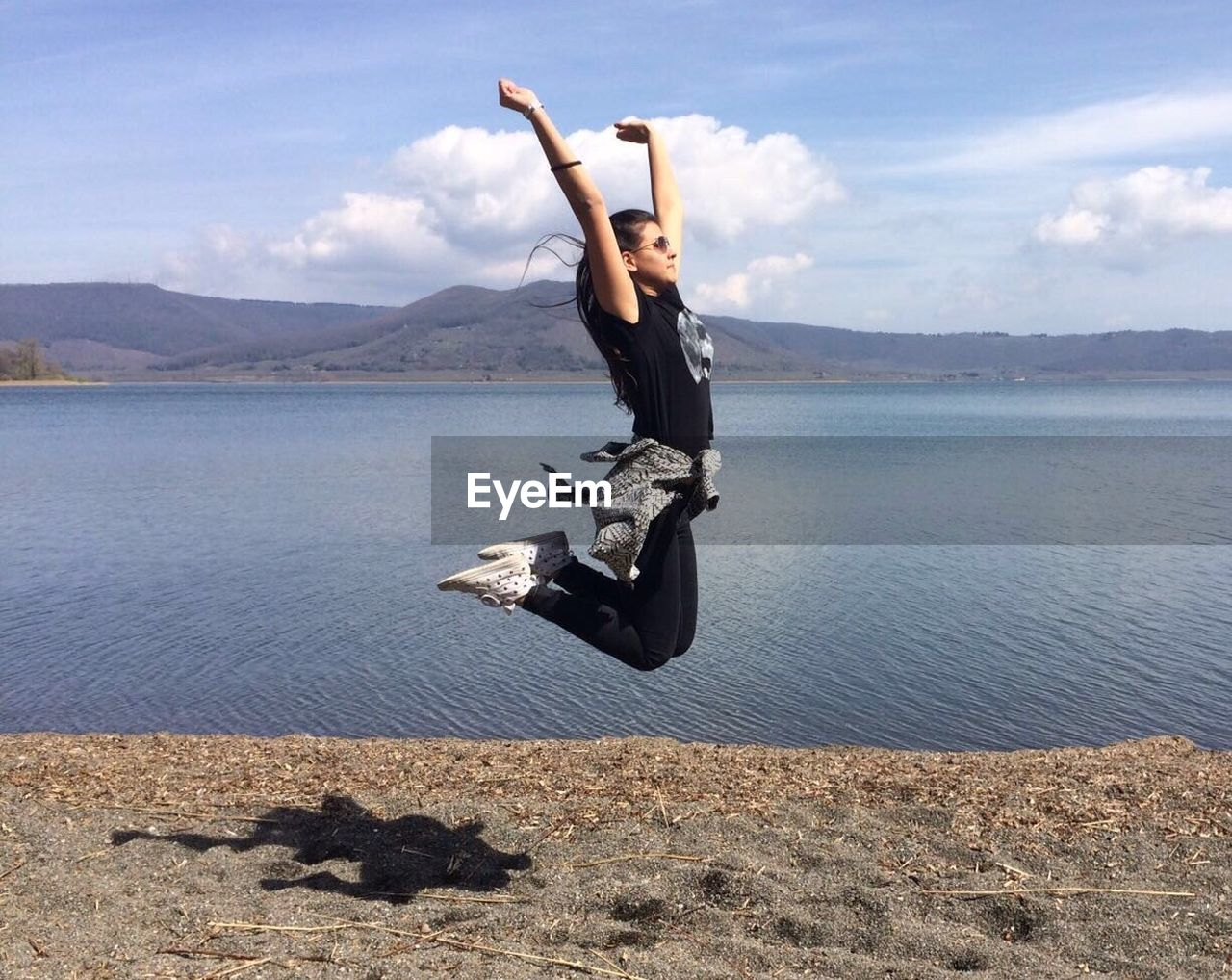 Side view of young woman jumping by lakeshore against sky