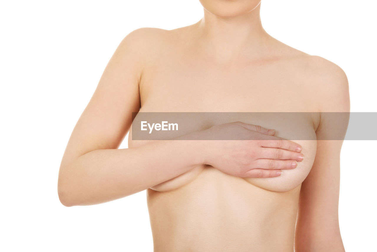Midsection of naked woman covering breasts against white background