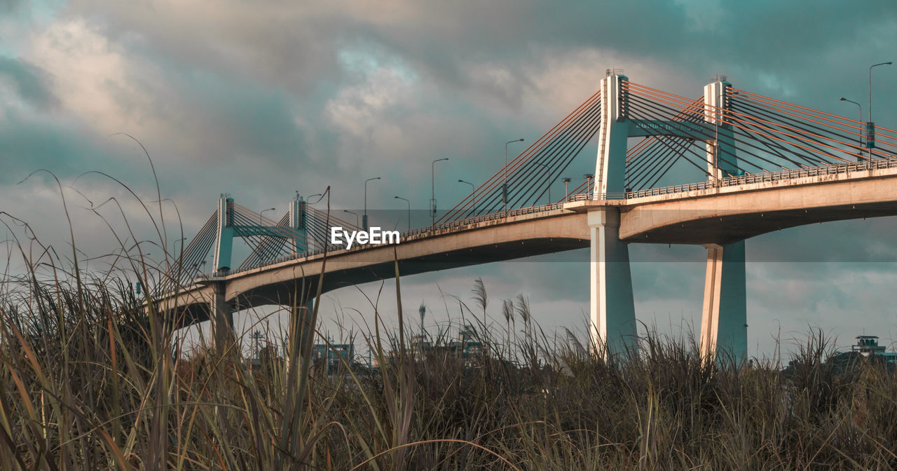 bridge, sky, bridge - man made structure, cloud - sky, connection, built structure, architecture, nature, transportation, engineering, plant, water, low angle view, grass, land, day, outdoors, long