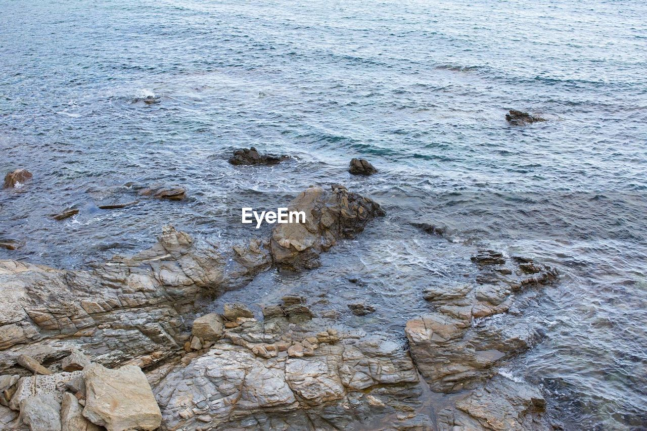 HIGH ANGLE VIEW OF ROCK FORMATIONS ON SEA