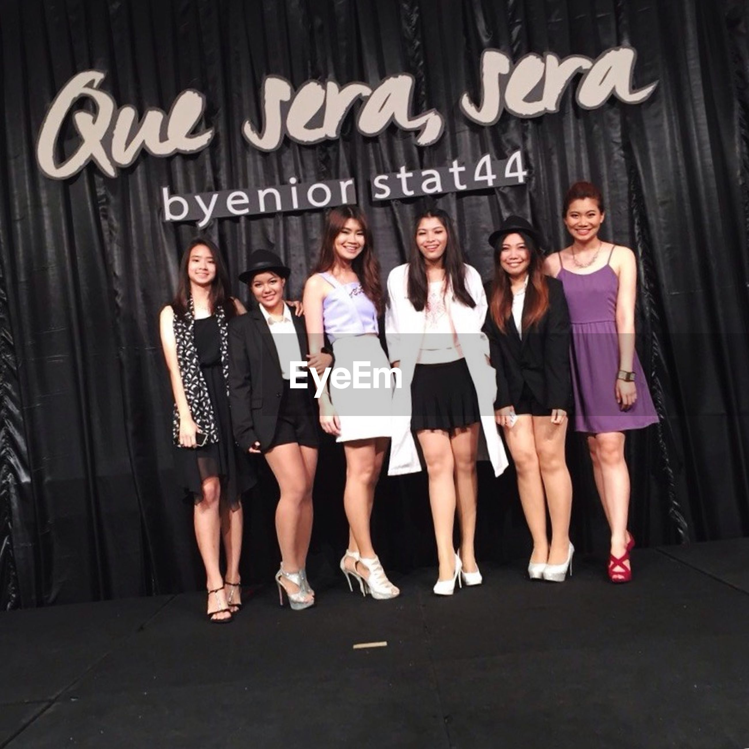 lifestyles, togetherness, leisure activity, front view, standing, bonding, casual clothing, young adult, friendship, indoors, love, young women, full length, person, side by side, text, wall - building feature