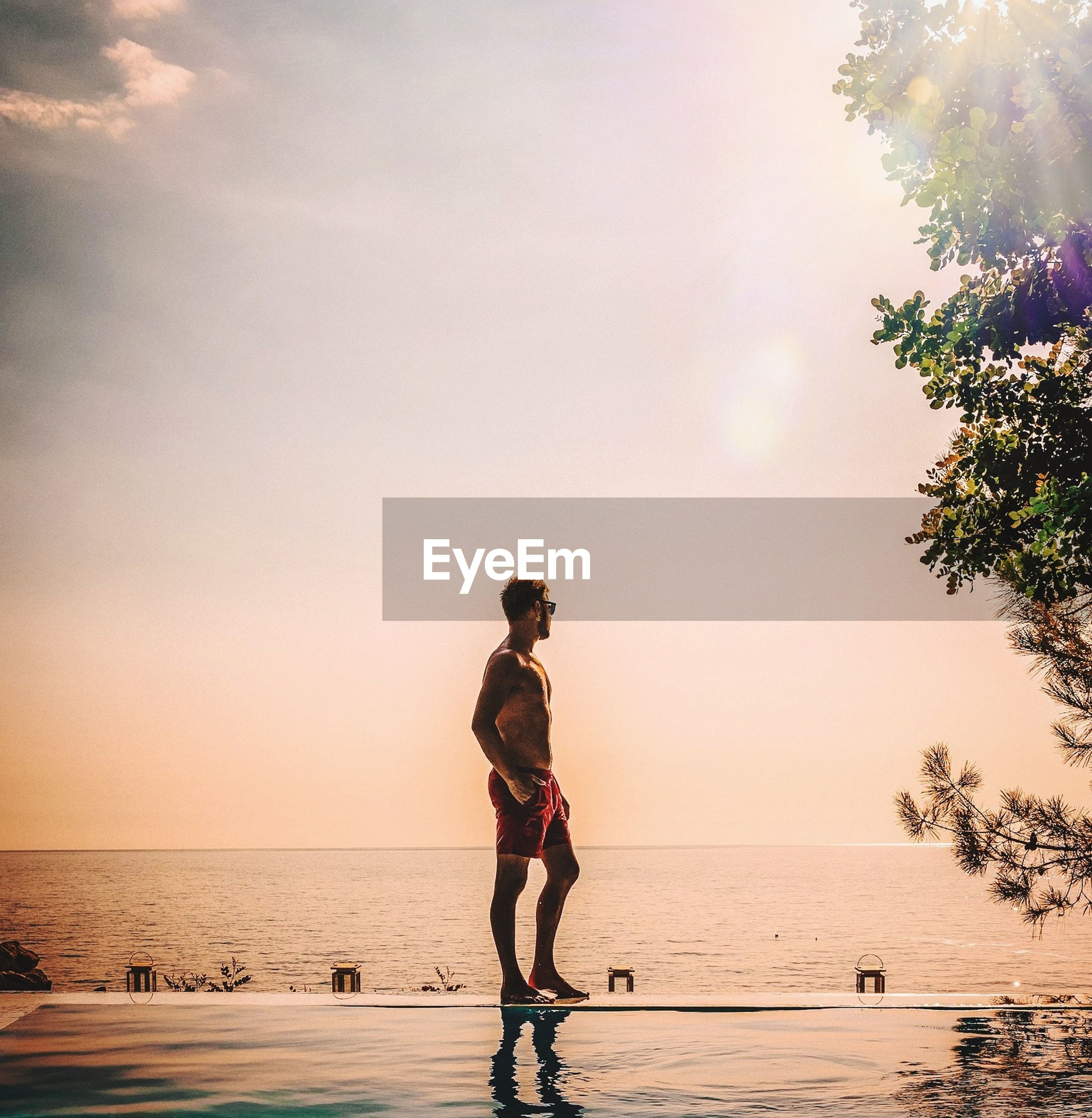 Full length of man standing on infinity pool against sky during sunset