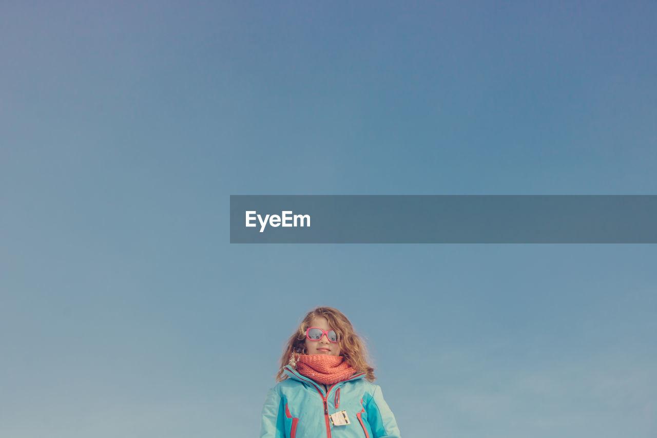 Portrait of girl against blue sky