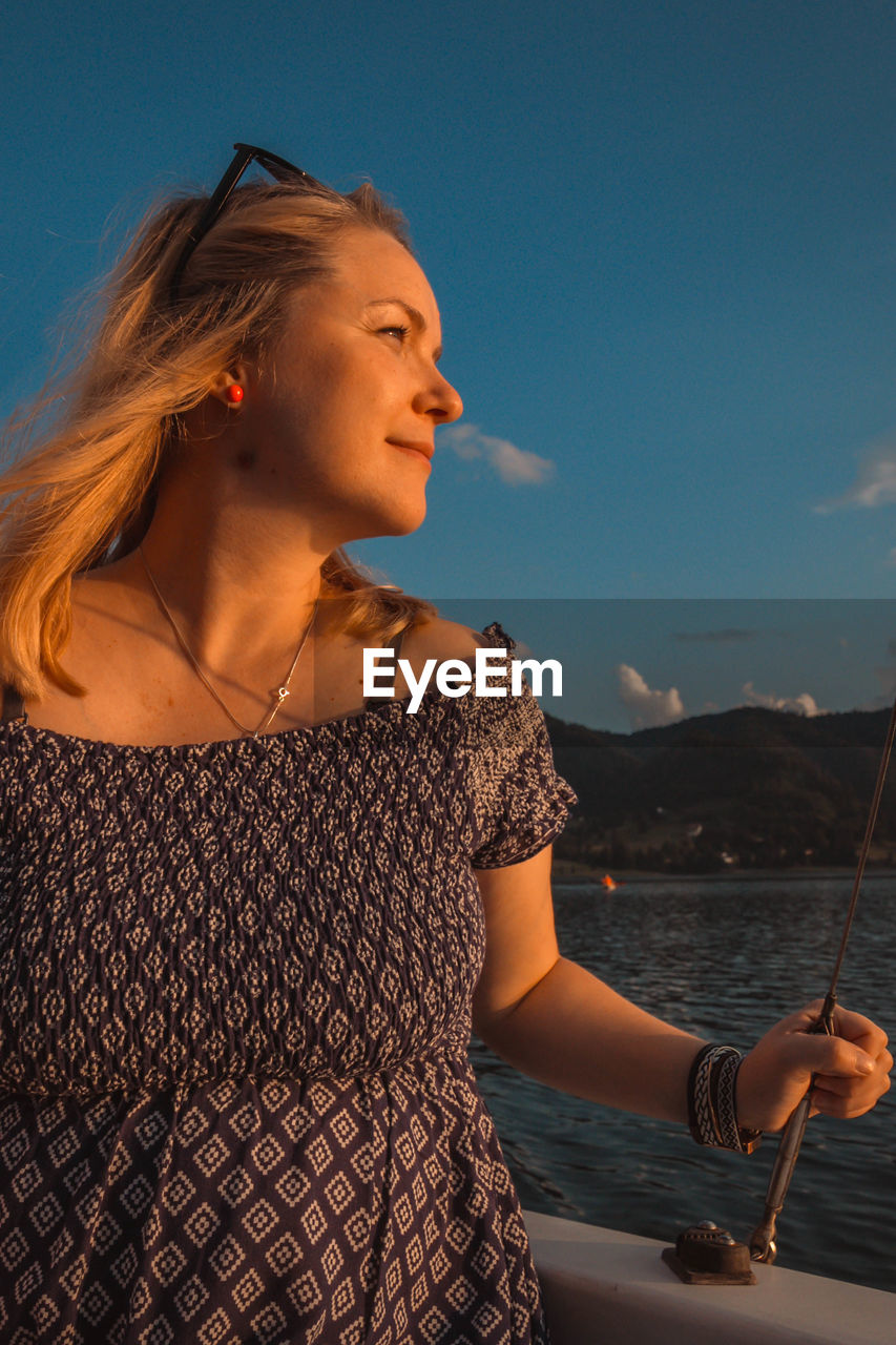 Mid adult woman looking away while standing in boat on sea against sky during sunset
