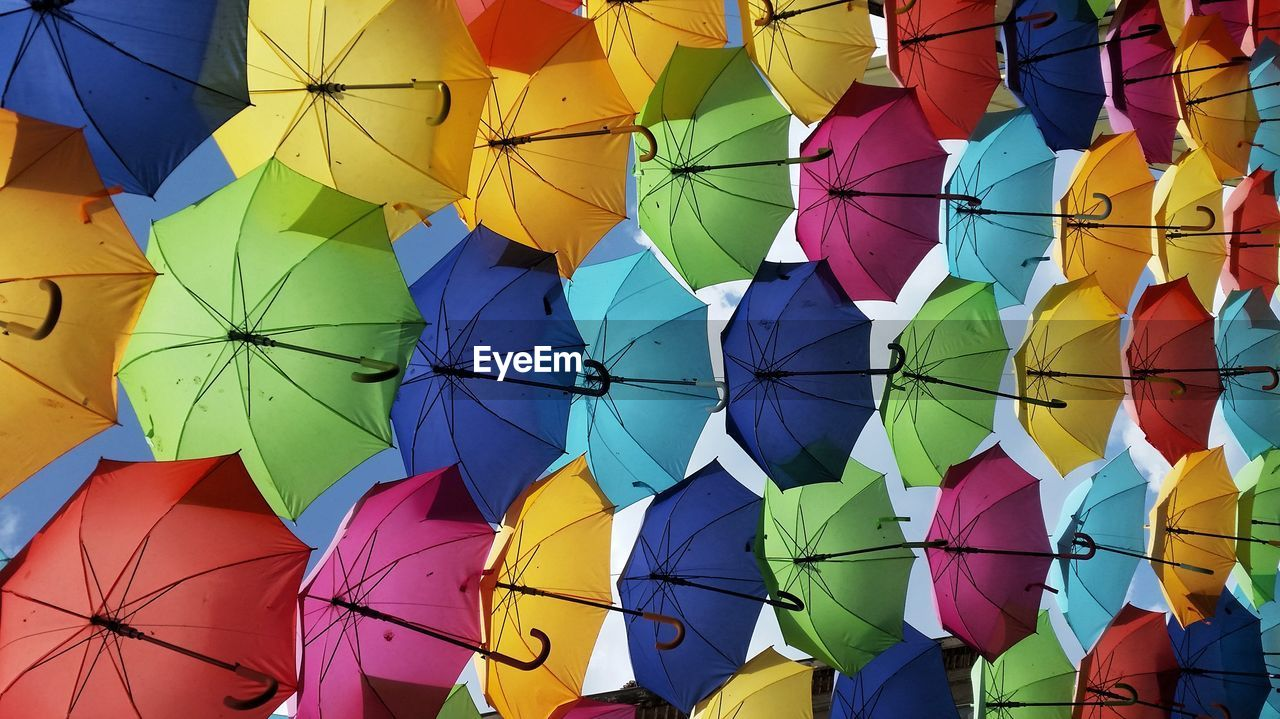 multi colored, large group of objects, no people, day, full frame, pattern, creativity, protection, variation, sunlight, hanging, choice, side by side, design, umbrella, abundance, outdoors, shape, backgrounds, low angle view