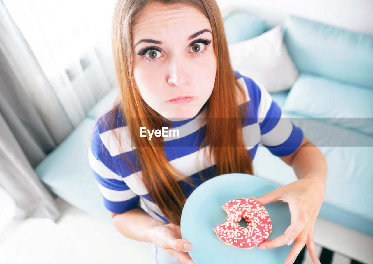 High angle view of woman eating donut