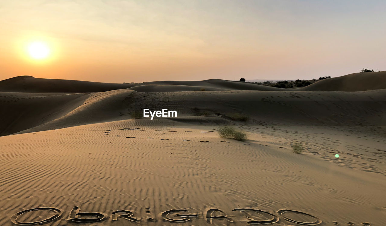 sand, land, scenics - nature, sky, sunset, beauty in nature, sand dune, tranquil scene, tranquility, desert, beach, nature, non-urban scene, landscape, arid climate, climate, idyllic, remote, water, environment, sun, no people, outdoors