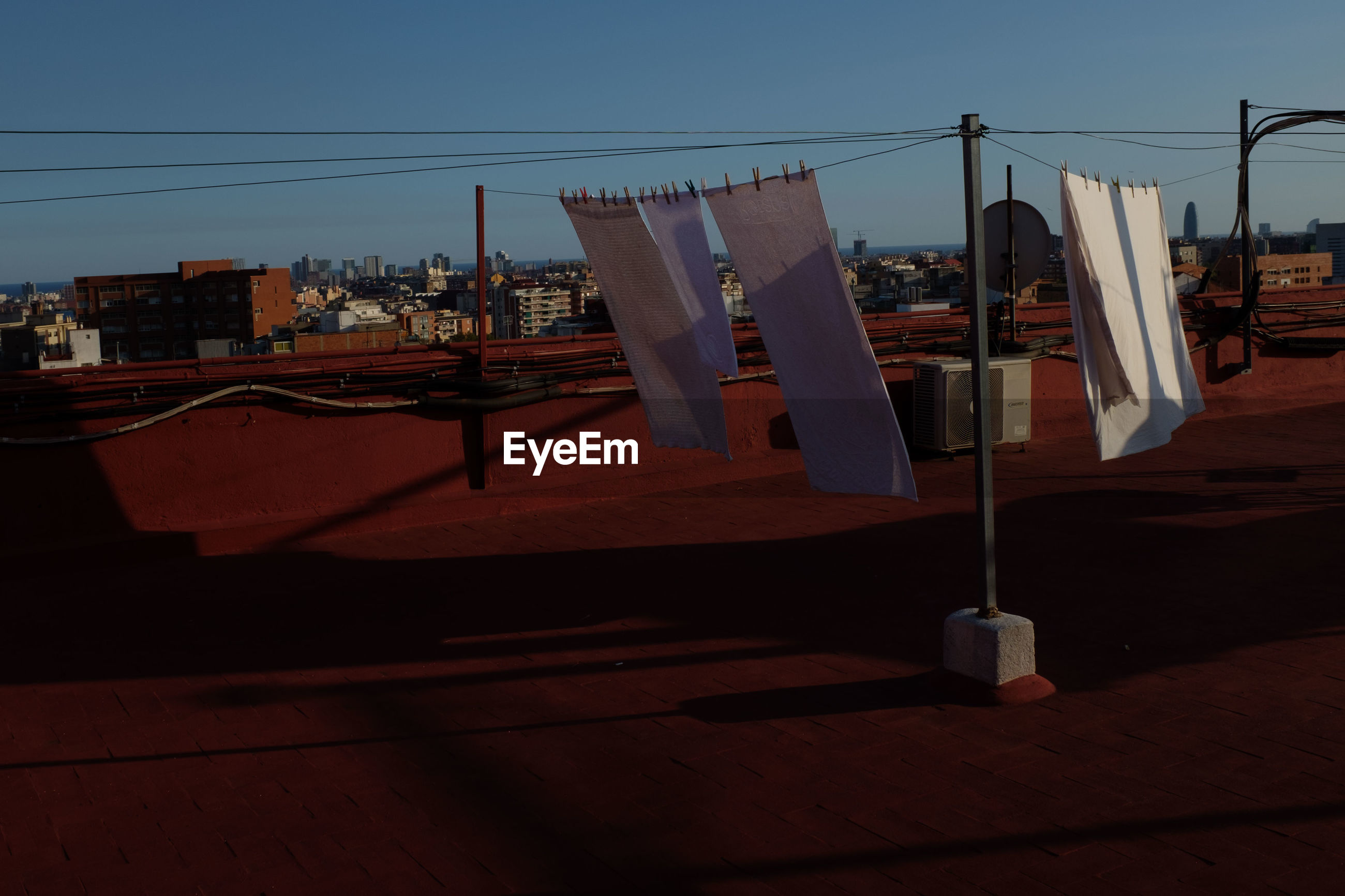 CLOTHES DRYING ON CLOTHESLINE AGAINST BUILDINGS