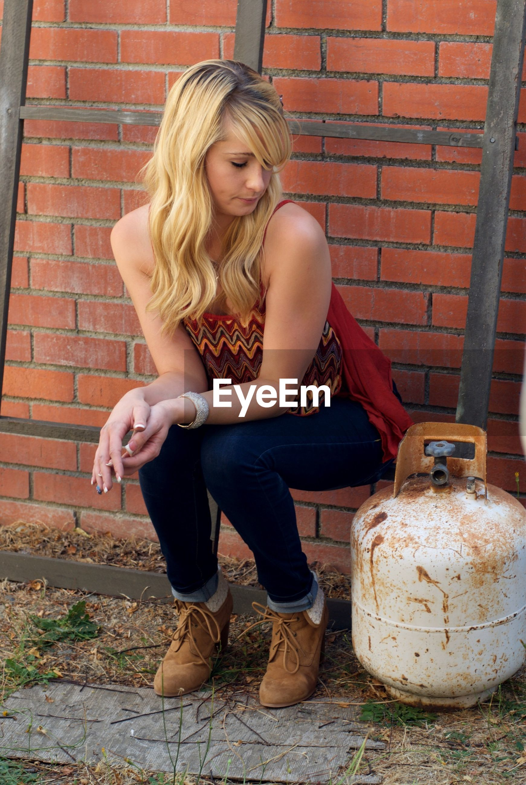 Young woman sitting on ladder while looking at cylinder against brick wall